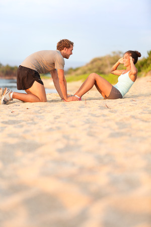 Young fitness couple working out doing situp crunches. Pretty asian fitness woman doing sit ups - caucasian male model helping kneeling happy smiling. Training crossfit on beach sand in sunset photo