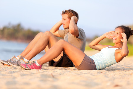 Situps training - young mixed race couple on beach sand in sunset happy smiling working out doing fitness crunches. Beautiful asian female and young caucasian fitness model Stock Photo