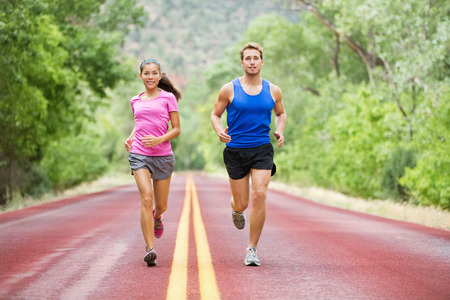 Running young multicultural couple exercising fitness outside on road in pretty nature jogging happy smiling. Asian female model and Caucasian male model training together. Stock Photo