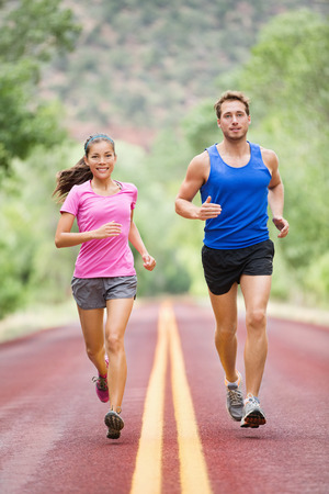 Running sporty people - two young runners jogging on road in nature training for marathon run. Multicultural couple, Asian woman sport model and man fitness model exercising together smiling happy Stock Photo
