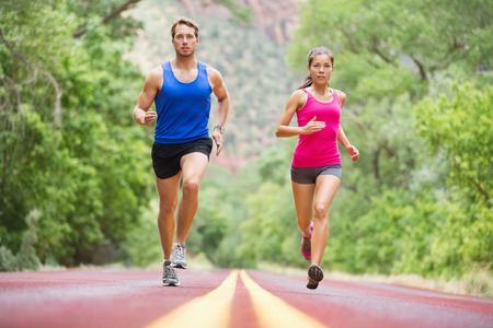 watch: Running young people - two runners jogging on road in nature training for marathon run. Multicultural couple - asian mixed race beautiful model woman and caucasian male fitness model exercising