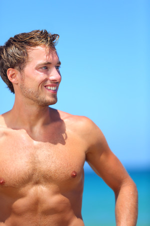beach hunk: Handsome good-looking man on beach smiling happy after swimming during vacation in holiday resort. Male model enjoying sunny holidays under the sun. Young Caucasian man in his twenties.