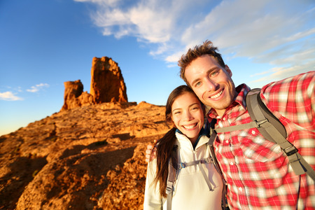 Selfie - Happy couple taking self portrait photo hiking. Two lovers or friends on hike smiling at camera outdoors mountains by Roque Nublo, Gran Canaria, Canary Islands, Spain. photo