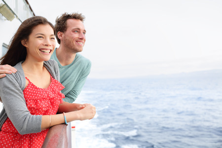 Cruise ship couple romantic on boat looking at view in romance. Happy lovers, woman and man traveling on vacation travel sailing on open sea ocean. Young Asian woman and Caucasian man. photo