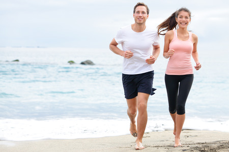 Exercising running couple jogging on beach. Runners training on sand by the ocean smiling happy in full body length. Interracial fit fitness couple, Asian woman and Caucasian man runner. Stock Photo