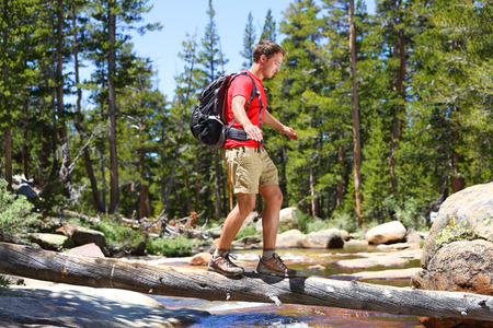 Hiker man hiking crossing river walking in balance on fallen tree trunk in Yosemite landscape nature forest. Happy male hiker trekking outdoors in Yosemite National Park., California, United States. Stok Fotoğraf