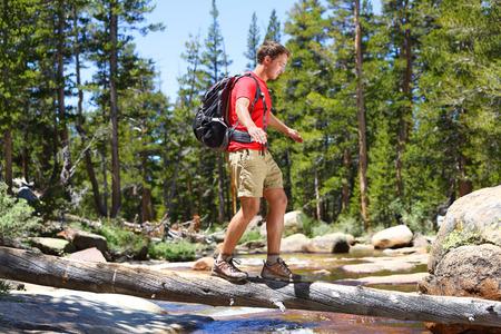 Wandelaar man wandelen oversteken rivier wandelen in balans op omgevallen boomstam in Yosemite landschap, natuur, bos. Gelukkig mannelijke wandelaar wandelen buiten in Yosemite National Park., California, Verenigde Staten.
