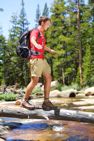 歩行バランスのヨセミテの風景自然の森で倒れた木の幹男交差の川をハイキングします。幸せな男性ハイカー トレッキング アウトドアでヨセミテ国 写真素材