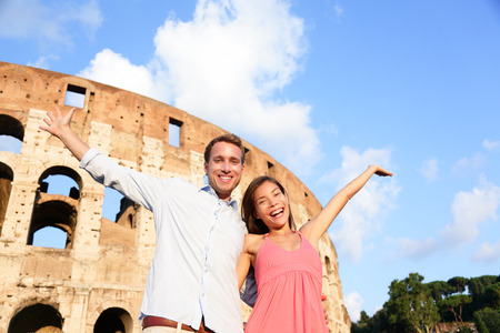 Rome couple happy by Colosseum travel fun cheering. Romantic couple embracing with arms up in Italy. Lovers on honeymoon sightseeing having fun by Coliseum. Love and travel concept multiracial couple. photo