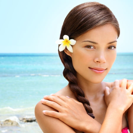 braided hair: Spa wellness beach beauty woman relaxing looking at camera on Hawaii beach. Beautiful serene and peaceful young mixed race Asian Caucasian female model on holiday travel resort. Flower in braided hair