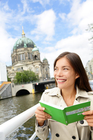 travel guide: Tourist woman on boat tour Berlin, Germany having fun smiling happy while enjoying mini cruise reading guidebook. Europe travel vacation holiday concept. Multiracial Asian Caucasian woman.