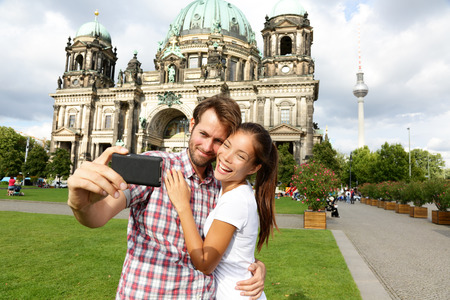 Berlin Germany travel couple selfie self portrait. Happy tourists people in front of Berlin Cathedral  Berliner Dom with Fernsehturm  Berlin TV Tower in the background. Asian woman, Caucasian man.