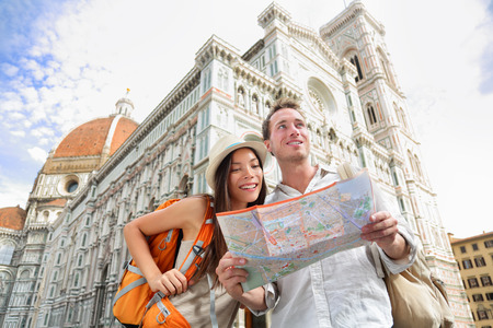 Tourist travel couple by Florence cathedral, Italy looking at map in front of Il Duomo di Firenze also called Basilica di Santa Maria del Fiore. Main tourist attraction and landmark in Florence, Italy 版權商用圖片