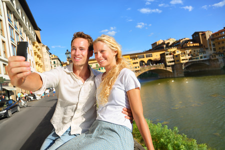 Happy couple selfie photo on travel in Florence. Romantic woman and man in love smiling happy taking self portrait outdoor by Ponte Vecchio during vacation holidays in Florence, Tuscany, Italy, Europe Stock Photo