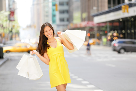 walking street: Urban shopping woman in New York City street with yellow taxi cab. Beautiful happy summer shopper holding shopping bags walking outside smiling. Multiracial Asian Caucasian model on Manhattan, USA. Stock Photo