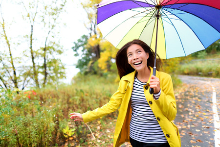 Autumn woman happy in rain running with umbrella. Female model looking up at clearing sky joyful on rainy fall day wearing yellow raincoat outside in nature forest by lake. Multi-ethnic Asian girl. photo