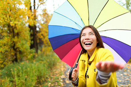 Umbrella woman in Autumn excited under rain on fall day.Beautiful young female wearing raincoat surprised and excited in the rain. Mixed race Asian Caucasian girl in her 20s walking in forest. photo