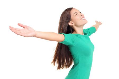 Adorare felice lodando gioiosa donna esultante con le braccia alzate aperte sorridente gioioso ed estatico piena di felicità con gli occhi chiusi isolato su sfondo bianco in studio. Femmina di razza mista. Archivio Fotografico