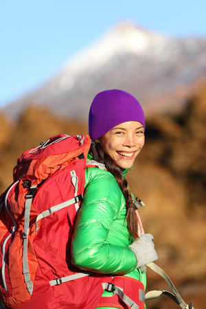 Hiking woman hiker living healthy lifestyle hiking outdoors wearing backpack smiling happy. Beautiful female trekking with looking with aspirations. Mixed race Asian Caucasian girl in her 20s. photo
