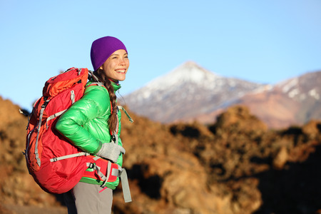 Active woman hiker living healthy lifestyle hiking outdoors wearing backpack smiling happy. Beautiful female trekking with looking with aspirations on Teide, Tenerife, Canary Islands, Spain, photo