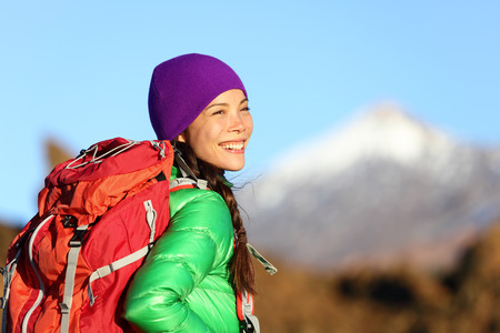 Active woman hiker living healthy lifestyle hiking outdoors wearing backpack smiling happy. Beautiful female trekking with looking with aspirations. Mixed race Asian Caucasian girl in her 20s. photo