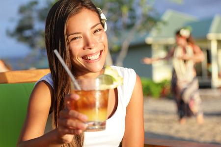 saúde: Mulher de beber álcool Mai Tai beber em Hawaii dando brinde dizendo cheers olhando a câmera no clube de praia. Menina bonita que aprecia bebida alcoólica cocktail. Mulher de sorriso feliz na praia havaiana.