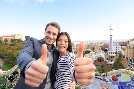 Travel couple happy in Park Guell, Barcelona, Spain. Beautiful young multiracial couple giving thumbs up hand sign smiling happy having fun on Europe vacation trip. Asian woman, Caucasian man. Stock Photo