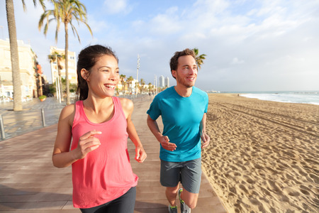 Running man and woman couple jogging on Barcelona Beach, Barceloneta. Healthy lifestyle people runners training outside on boardwalk. Multiracial couple, Asian woman, Caucasian fitness man working out Фото со стока