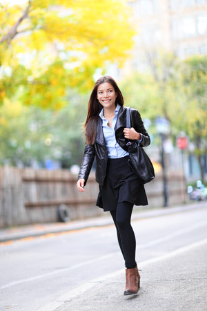 Young urban professional woman in walking in city. Fashion girl living city lifestyle in leather jacket in autumn fall. Trendy modern female. Multiracial Asian Caucasian model. Stock Photo