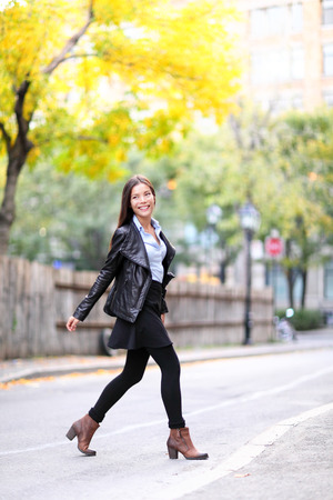Fashion urban young woman living city lifestyle walking in leather jacket crossing streets in full length in autumn fall. Trendy modern female. Multiracial Asian Caucasian model.