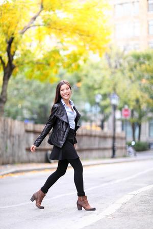 Mode urbaine jeune femme vivant mode de vie urbain marche dans les rues de la veste en cuir de passage dans la pleine longueur à l'automne automne. Femelle dernier cri moderne. Caucasien asiatique modèle multi-ethnique. Banque d'images - 28635951