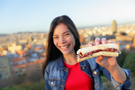 Jamon Iberico Sandwich. Woman eating in Barcelona, Spain showing traditional Spanish food, cured Serrano ham. Focus on bocadillo, Barcelona skyline in background. Stock Photo - 28636047
