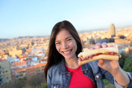 Jamon Serrano Sandwich. Woman eating in Barcelona, Spain showing traditional Spanish food, cured Iberico ham. Focus on girl, Barcelona skyline in background. Stock Photo - 28636051