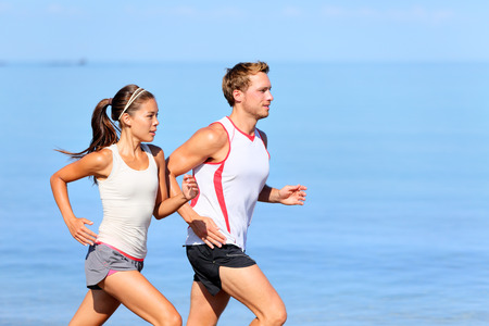 Running couple jogging on beach. Runners training together. Man and woman joggers exercising outdoors. Stock Photo