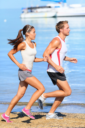 Running couple. Runners jogging on beach training together. Man and woman joggers exercising outdoors. photo