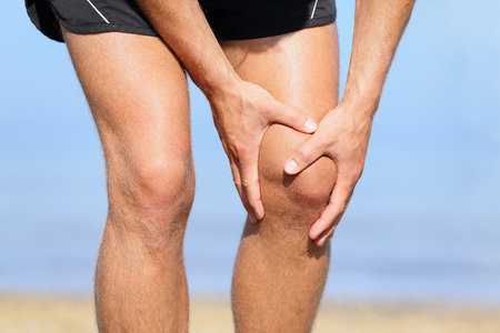 Runner injury - Man running with knee pain. Close-up view of runner injured jogging on the beach clutching his knee in pain. Male fitness athlete. Stock Photo