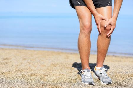 달리기 부상 - 무릎 통증으로 조깅하는 사람 (남자). 주자의 근접 촬영보기 고통에 무릎을 쥐고 해변에서 조깅 부상. 남성 피트니스 선수. 스톡 콘텐츠