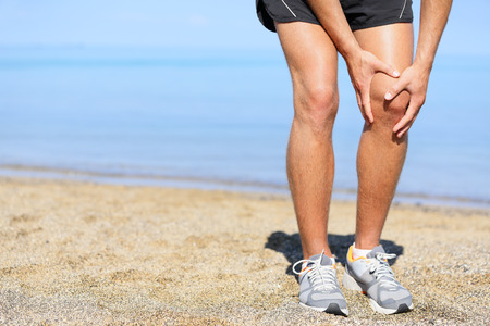 injured knee: Running injury - Man jogging with knee pain. Close-up view of runner injured jogging on the beach clutching his knee in pain. Male fitness athlete. Stock Photo
