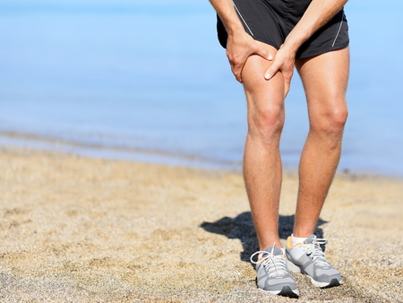 Muscle injury. Runner man with sprain thigh muscle. Athlete in sports shorts clutching his thigh muscles after pulling or straining them while jogging on the beach wearing running shoes. Фото со стока