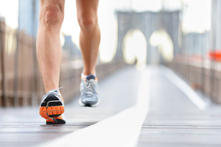 Running shoes, feet and legs close up of runner jogging in action and motion on Brooklyn Bridge, New York City, USA Stock Photo