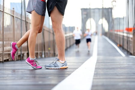 Kissing couple running - Love sport romantic dating concept. Closeup of running shoes and girl standing on toes to kiss boyfriend during jogging workout training on Brooklyn Bridge, New York City, USA