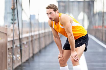 Esecuzione di uomo di riposo dopo l'esecuzione in New York City. Formazione Runner e jogging esterno prendendo una pausa. Caucasica corridore maschile e sport modello di fitness sul Ponte di Brooklyn, New York City, USA.