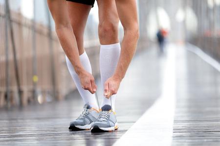 Hardloopschoenen - Runner man koppelverkoop veters, New York City op Brooklyn Bridge. Mannelijke atleet loper en voeten close-up. Fitness model dragen van compressie sokken.