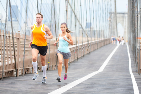 Running couple. Runners jogging outside on run. Asian woman and Caucasian man runner and fitness sport models training outdoors on Brooklyn Bridge, New York City, USA. Stock Photo - 29880225