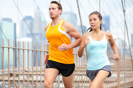 Running couple jogging training for New York marathon. Runners on run outside. Asian woman and Caucasian man runner and fitness sport models jogging on Brooklyn Bridge, New York City, USA. Stock Photo