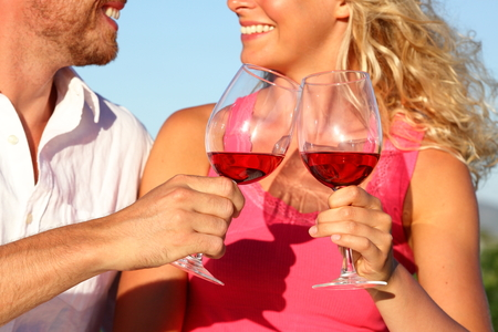 Toasting wine drinks - couple drinking glasses red or rose. Closeup of hands and mouth photo