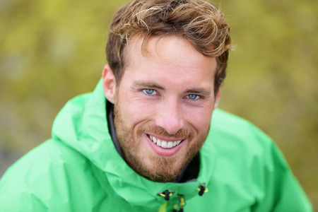 Happy man hiking portrait in nature outdoors. Handsome caucasian male smiling.