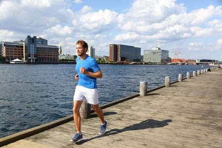 Running man joggen in de moderne stad. Mannelijke agent te oefenen op Kopenhagen promenade in Bryggen, Denemarken.