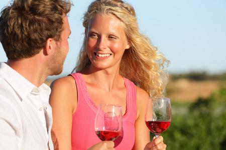 Happy couple drinking wine in sunset.  photo
