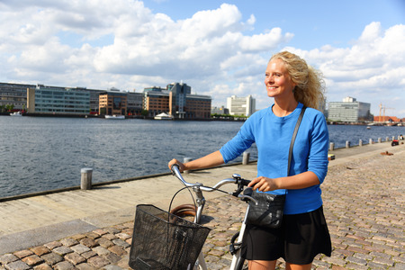 Danish woman walking in Copenhagen harbour with bicycle.  photo
